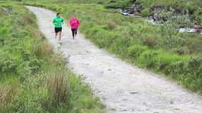 Fit couple jogging together on a trail. In the countryside stock video footage