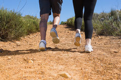 Fit couple jogging up mountain trail Stock Photos