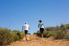 Fit couple jogging up mountain trail Royalty Free Stock Photo