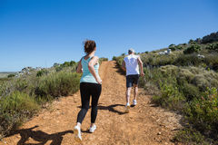 Fit couple jogging up mountain trail Royalty Free Stock Photography