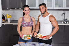 Fit couple in the kitchen, holding plates of food Royalty Free Stock Photos