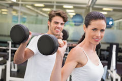 Fit couple lifting barbells together Royalty Free Stock Photo