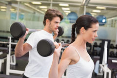 Fit couple lifting barbells together Royalty Free Stock Photos