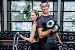 Fit couple lifting dumbbells back to back Royalty Free Stock Photo