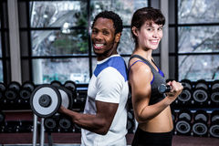 Fit couple lifting dumbbells back to back Stock Photography