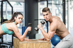 Fit couple lifting dumbbells Stock Photo