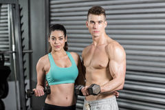 Fit couple lifting dumbbells and looking at the camera Royalty Free Stock Photos