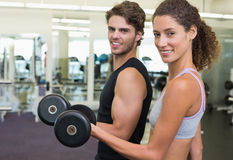 Fit couple lifting dumbbells together smiling at camera Royalty Free Stock Image