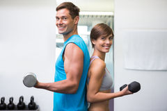 Fit couple lifting dumbbells together smiling at camera Stock Images