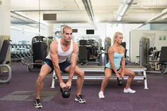 Fit couple lifting kettle bells in gym Royalty Free Stock Photos