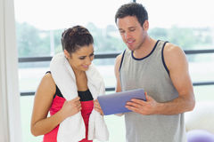Fit couple looking at digital table in exercise room Stock Images