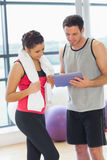 Fit couple looking at digital table in exercise room Royalty Free Stock Image