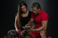 Fit Couple Looking At Digital Table. In A Studio On A Black Background Stock Image