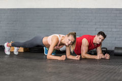 Fit couple planking together in gym Royalty Free Stock Image