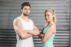 Fit couple posing with arms crossed Royalty Free Stock Images