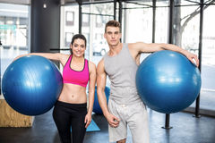 Fit couple posing with sport ball Royalty Free Stock Images