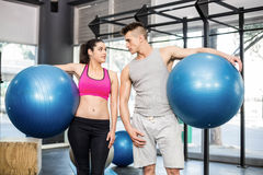 Fit couple posing with sport ball Stock Images