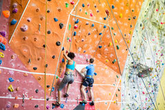 Fit couple rock climbing indoors Stock Image