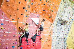 Fit couple rock climbing indoors Royalty Free Stock Photography