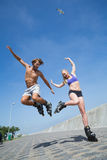 Fit couple rollerblading together on the promenade Royalty Free Stock Images