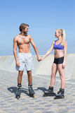 Fit couple rollerblading together on the promenade Stock Photo