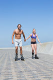 Fit couple rollerblading together on the promenade Royalty Free Stock Photography