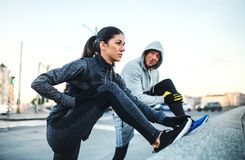 A fit couple runers doing stretching outdoors on the bridge in Prague city. A fit sporty couple runners doing stretching outdoors on the bridge in Prague city stock photos