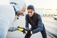 A fit couple runners measuring time outdoors on the streets of Prague city. A fit sporty couple runners measuring time on a smartwatch outdoors on the streets stock photo