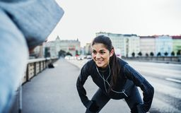 A fit couple runners stretching outdoors on the streets of Prague city. A fit sporty couple with earphones runners stretching outdoors on the streets of Prague stock photo