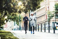 A fit couple running outdoors on the streets of Prague city. stock photo