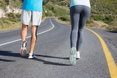 Fit couple running together down a road. On a sunny day Stock Images