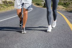 Fit couple running together up a road. On a sunny day Stock Photos