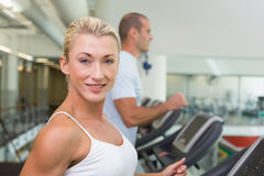 Fit couple running on treadmills at gym Royalty Free Stock Image