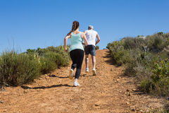 Fit couple running up mountain trail Royalty Free Stock Photo