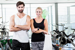 Fit couple smiling at the camera with arms crossed. At the gym Royalty Free Stock Photography