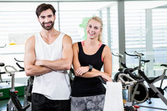 Fit couple smiling at the camera with arms crossed. At the gym Stock Photography