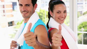Fit couple smiling at camera. At the gym stock footage