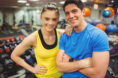 Fit couple smiling at camera. At the gym Royalty Free Stock Photos