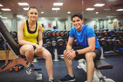Fit couple smiling at camera. At the gym Stock Images