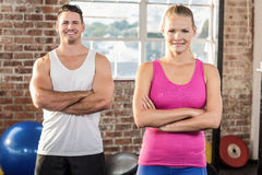 Fit couple smiling face to the camera. In crossfit gym Stock Photography