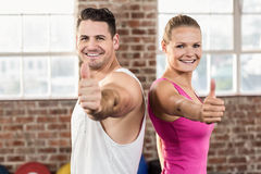 Fit couple smiling gesturing thumbs up. In crossfit gym Stock Images