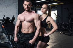 Fit couple in sportswear posing together at gym. Young fit couple in sportswear posing together at gym Royalty Free Stock Images