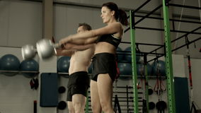 Fit couple squatting with kettlebells stock video footage