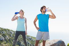 Fit couple standing drinking from water bottles Royalty Free Stock Images