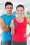 Fit couple standing with dumbbell in bright exercise room Royalty Free Stock Photos