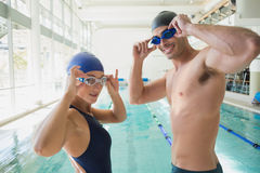 Fit couple swimmers by pool at leisure center. Portrait of a fit male and female swimmers by the pool at leisure center Royalty Free Stock Images
