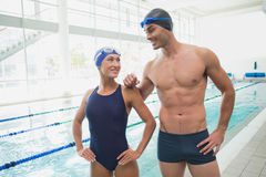 Fit couple swimmers by the pool at leisure center. Portrait of a fit male and female swimmers by the pool at leisure center Royalty Free Stock Image