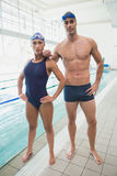 Fit couple swimmers by the pool at leisure center. Portrait of a fit male and female swimmers by the pool at leisure center Stock Image
