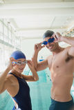 Fit couple swimmers by pool at leisure center. Portrait of a fit male and female swimmers by the pool at leisure center Stock Photos