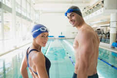 Fit couple swimmers by pool at leisure center Royalty Free Stock Photo